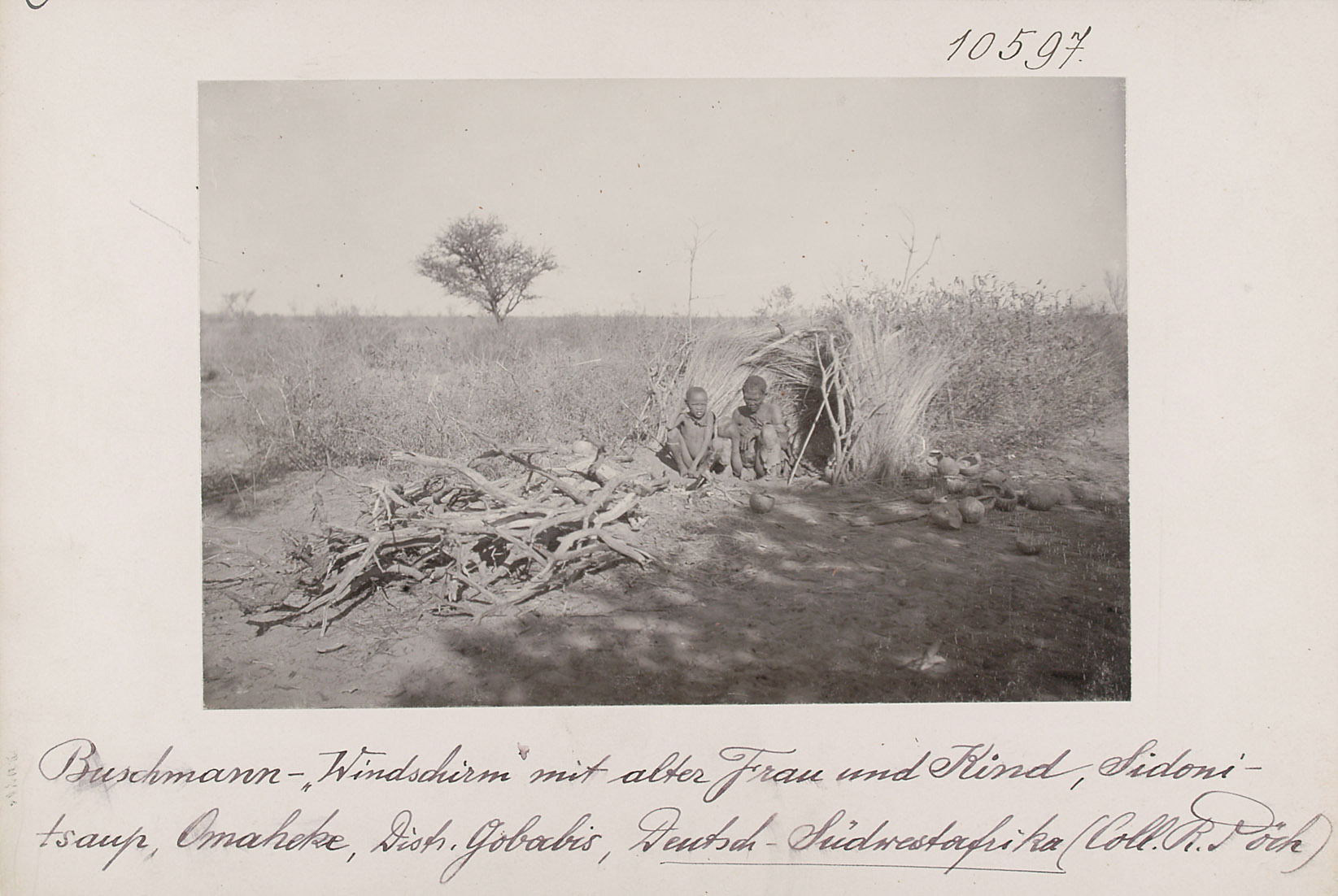 """San-""""Windschirm"""" mit alter Frau und Kind, Sidonitsaup, Omaheke, Distr. Gobabis, Deutsch-Südwestafrika von Rudolf Pöch"""
